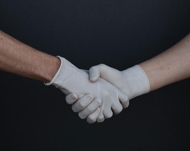 Shaking hands wearing gloves